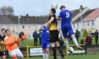 Cove's Mitchel Megginson climbs highest to meet a cross, but his header was wide of goal.