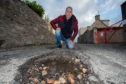 Councillor Gordon Cowie on Harbour House Lane in Buckie where the pot holes have developed over time.