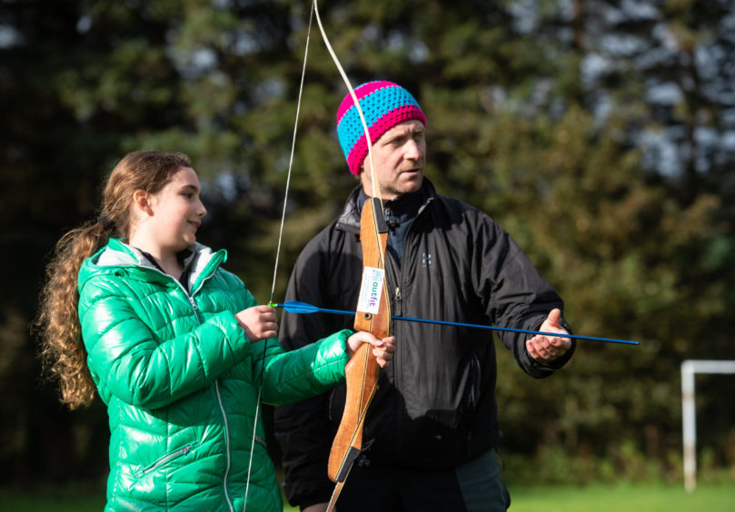 Maisie Anthony, 9 receives archery tuition from Steve Glew from Outfit Moray. Picture by JASON HEDGES