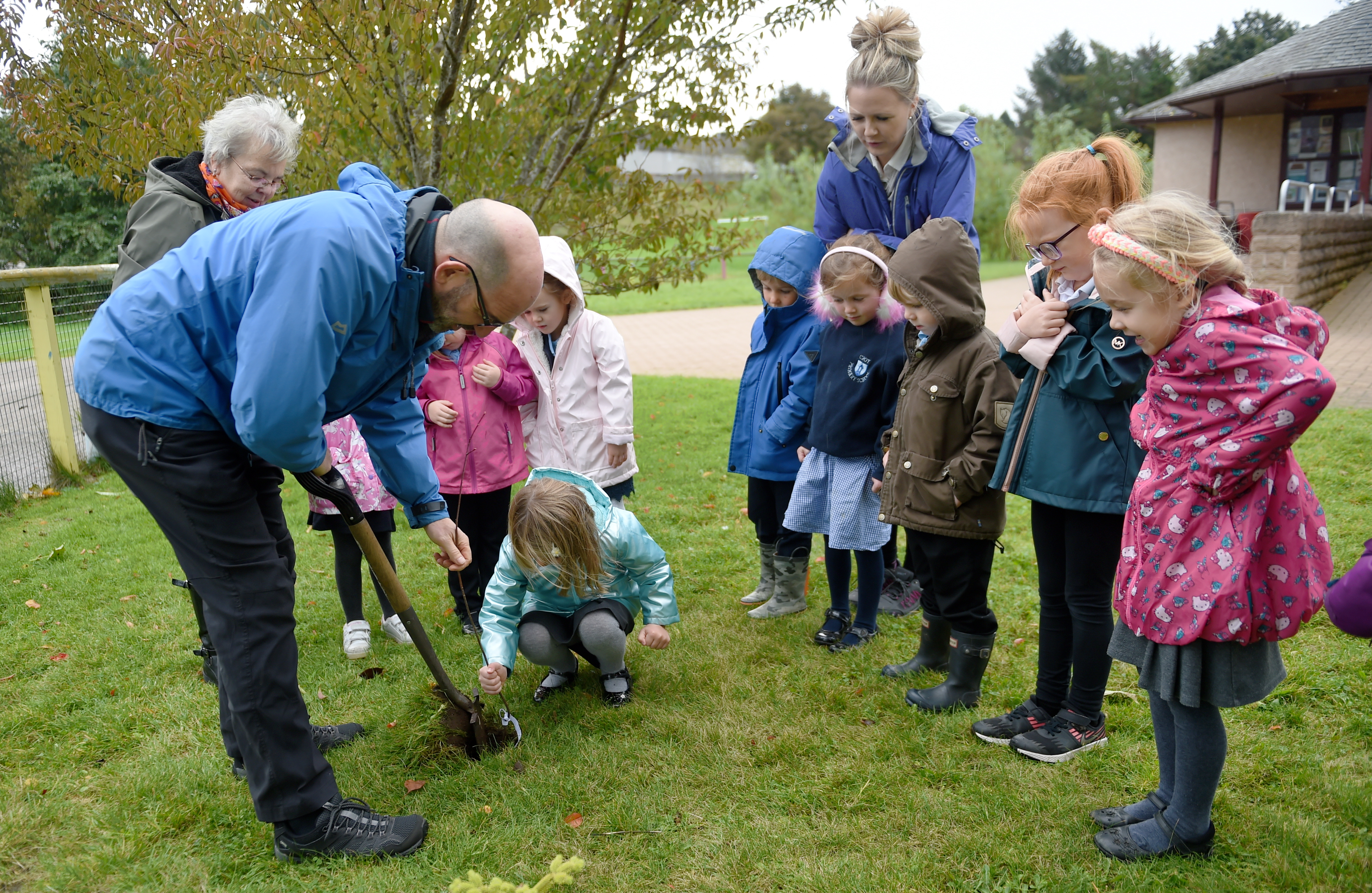 Pupils of Primary 1 in Croy Primary School yesterday planted trees in the school grounds. Highland Coumcil Forestry Officer Grant Stuart helps the pupils plant the trees.