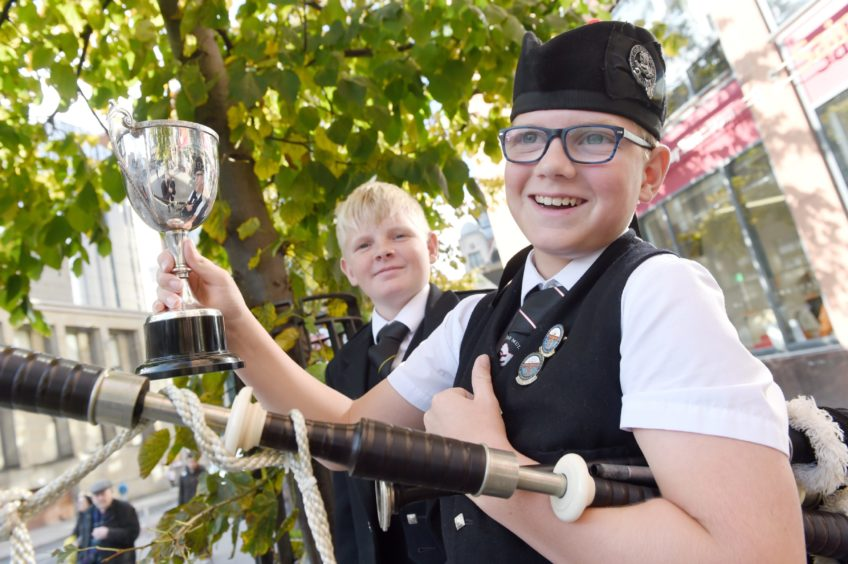 Archie Johnston (right) of Mull with the Roderick Ross, Ferintosh, Memorial Trophy for piping in the under 13 age groups. Also in the photograph is his brother Logie who won the same cup at last year's Mod in Dunoon. Picture by Sandy McCook
