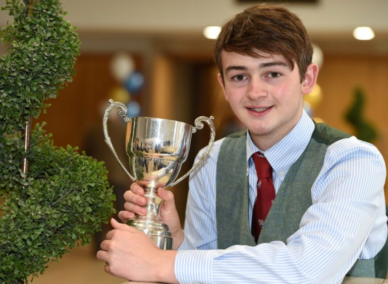Finlay Cameron of Roy Bridge with the John T MacRae Cup for four part March, Strathspey and Reel in the adult piping competitions. Picture by Sandy McCook