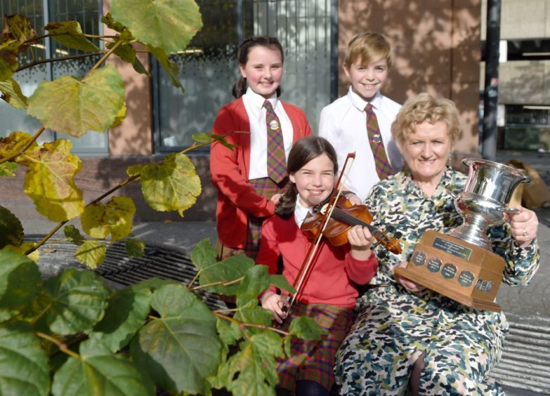 Highland Councillor Biz Campbell presents some members of the folk group Clann le Ceol with the Murdo MacFarlane Trophy and the Highland Council Prize. At the rear are Guilia Gordon and Sorley Cavanagh while in the front with the fiddle is Sophie Fuge. Picture by Sandy McCook.