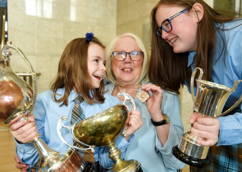 Mary Maclean of the Falkirk Gaelic School  who herself won the Mod Gold Medal exactly fifty years ago at the Aviemore Mod with her two grandaughters Rachel (9) and Rebecca (14) with some of the choirs silverware from their competitions. Picture by Sandy McCook.