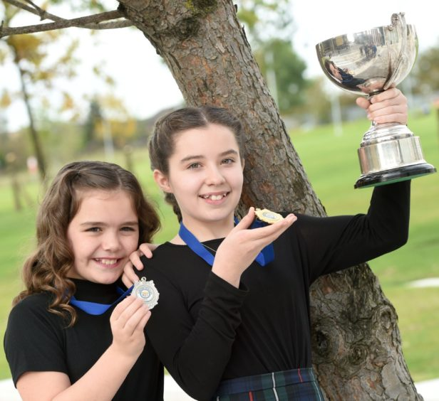 Kyla Mackenzie of Lochs in Lewis with the Ronald MacEachan Memorial Cup for solo singing in the girls 11-12 age group. Also in the photograph is runner up Aimee MacLeod also of Lochs. Picture by Sandy McCook.