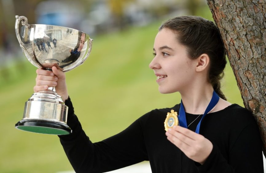 Kyla Mackenzie of Lochs in Lewis with the Ronald MacEachan Memorial Cup for solo singing in the girls 11-12 age group. Picture by Sandy McCook.