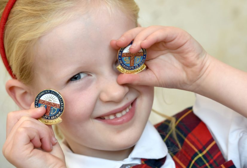 Proudly showing off her two gold badges, Tess Fleming from Glendale Primary in Glasgow winning in both prose and singing. Picture by Sandy McCook.