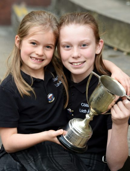 Layla Orr-MacIntyre (12) of the Lochaline Choir (right) with the John Mackenzie Paterson Memorial Trophy for recitation of prescribed poetry while also in the photograph is little sister Kara (7), also a member of the choir and winner of the Hugh Macintyre Memorial Trophy for solo singing in the 7 year old age group. Picture by Sandy McCook.