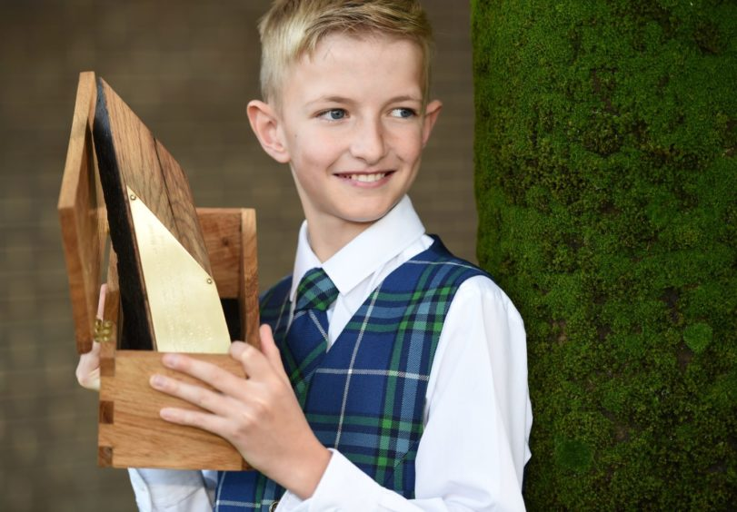Luke Johnsson of the Sir E Scott School, Tarbert, Harris with the Tom and Rae Mitchell Memorial Trophy for traditional singing in the under 13 category. Picture by Sandy McCook.