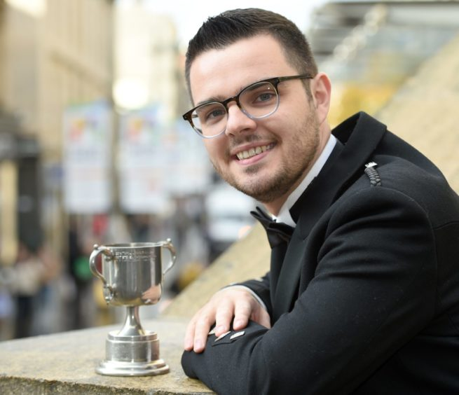 Alasdair Iain MacPhee of Glasgow with the Rotary Club of Lochaber Trophy in the men's Traditional singing competition and a qualifier for the Gold Medal. Picture by Sandy McCook.