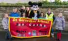 28 October 2019. St Gerardines Primary School, Lossiemouth, Moray, Scotland, UK. This is Lossiemouth Community Council bid to collect pennies to make up a mile relative to Safer Crossings with P4 pupils of St Gerardines School. L- R - Flo Selllar, Mathew Simpson, Phoebe Cannon, Louise McBride with her daughter, Carolle Ralph as Mickey, Charlotte Stewart, Kirsty Middleton and Taylor Murray