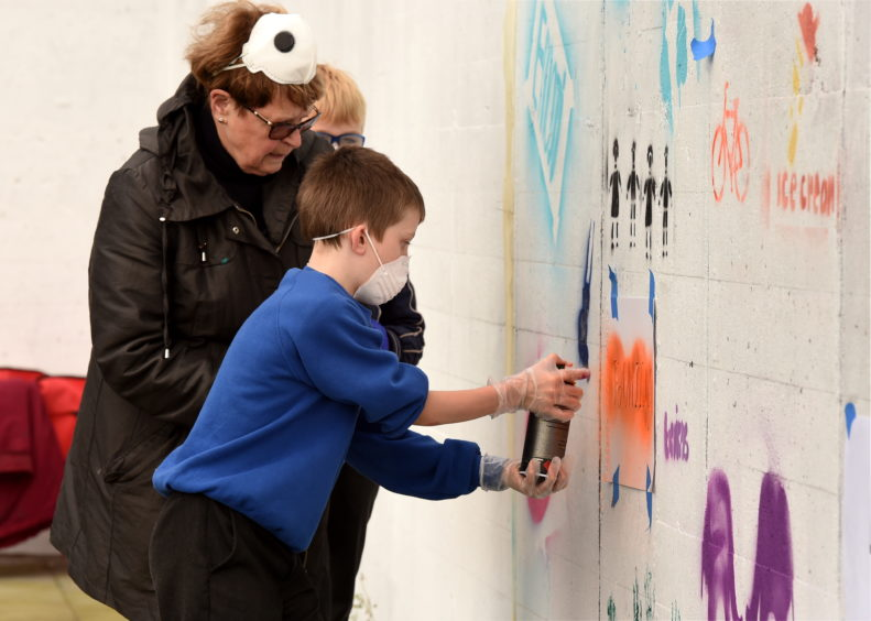 Dorothy Borthwell and Callum Roy painting the wall.
