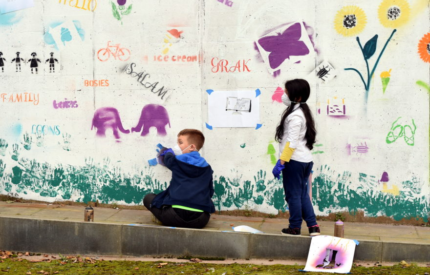 The Gilcomstoun School kids spray-painting a white wall at the park across the road from the school on Skene Street.