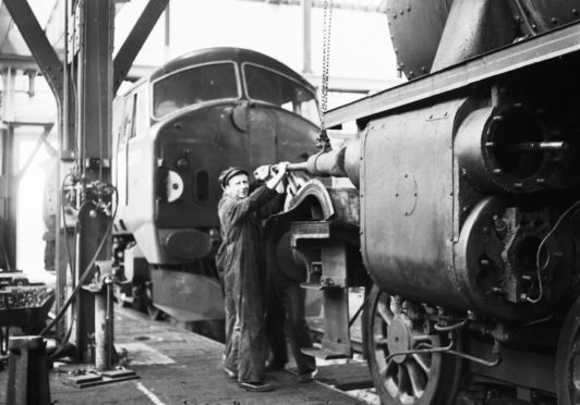 "AN Inverurie Loco Works 1962-08-28_5 (C)AJL Neg.No. G149 ""Workmen at the Inverurie Loco Works working on the piston of a steam engine in 1962."""