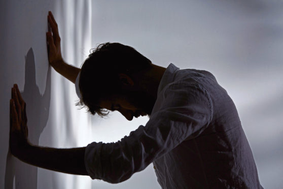 Man leaning with hands against wall, dark room