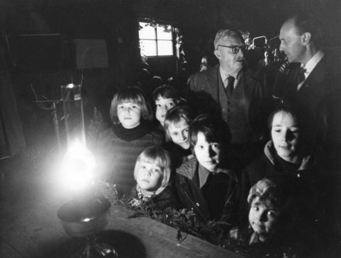 An oil lamp casts a gentle glow on the faces of Corgarff children awaiting the hook-up of the village to the National Grid.