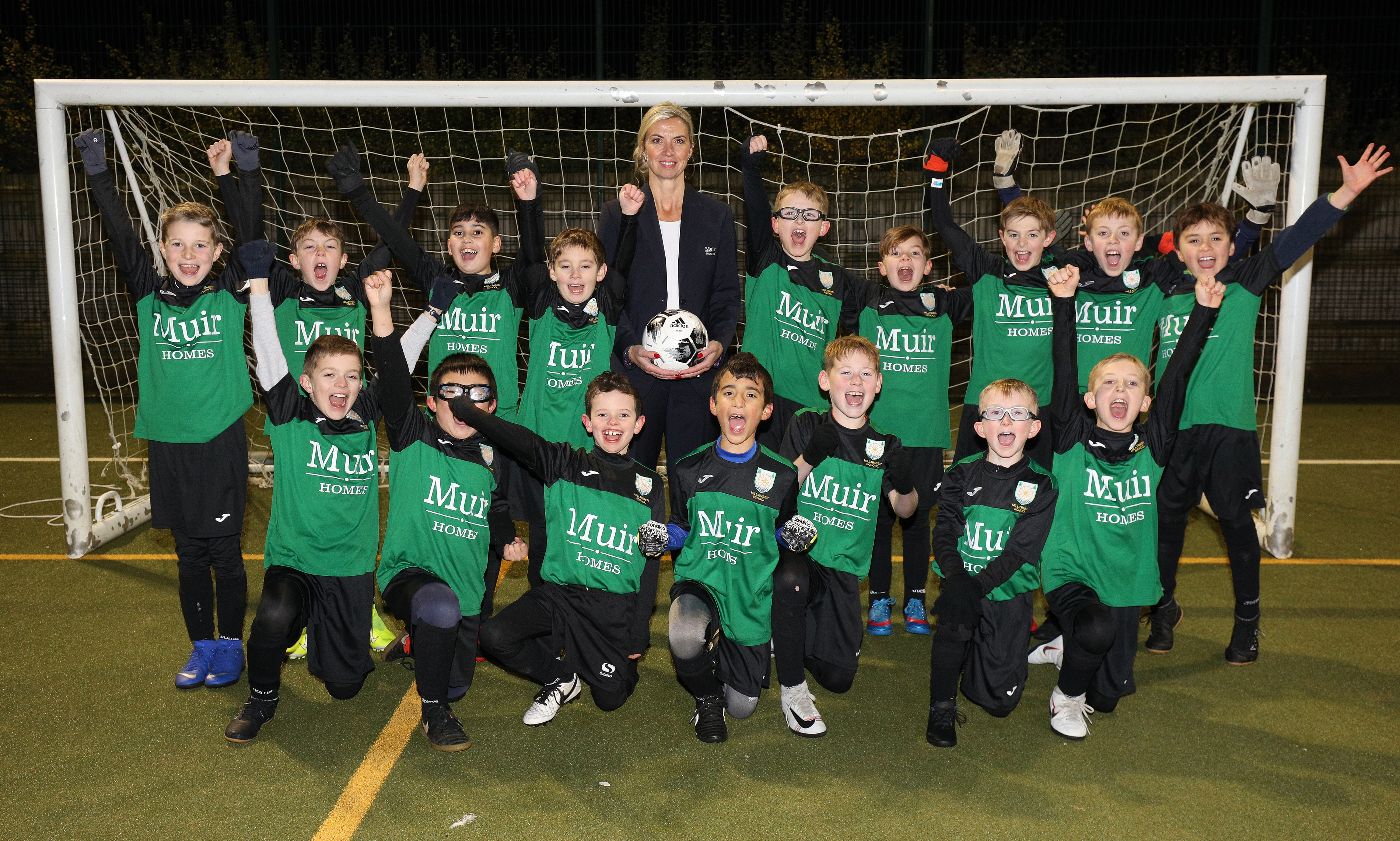 Primary 5 Milltimber school football team with Louise Craig, sales advisor for Muir Homes.