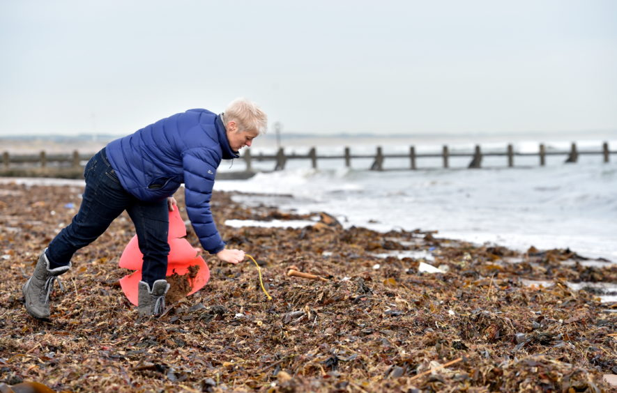 A pile of plastic has washed up on the beach and a concerned resident is worried it will be washed back into the sea when the tide comes in. Pictured is Gail Dicksman picking up some of the rubbish washed up on Aberdeen Beach. Pictured on 19/11/2019 CR0016578