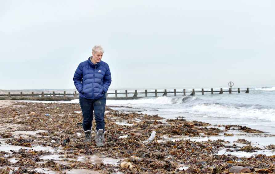 Gail Dicksman picking up some of the rubbish washed up on Aberdeen Beach.