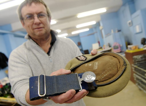 Inverbervie auctioneer Dave Smith pictured with the rare soldier's belt and hat that he has found.   Picture by KATH FLANNERY