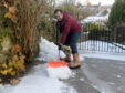Albert Booth shovels snow off his neighbour's drive, Huntly. Picture by KATH FLANNERY