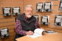 Ian Cheyne (also known as Will B Justice) signing copies of his new book of poems  Picture by Paul Glendell