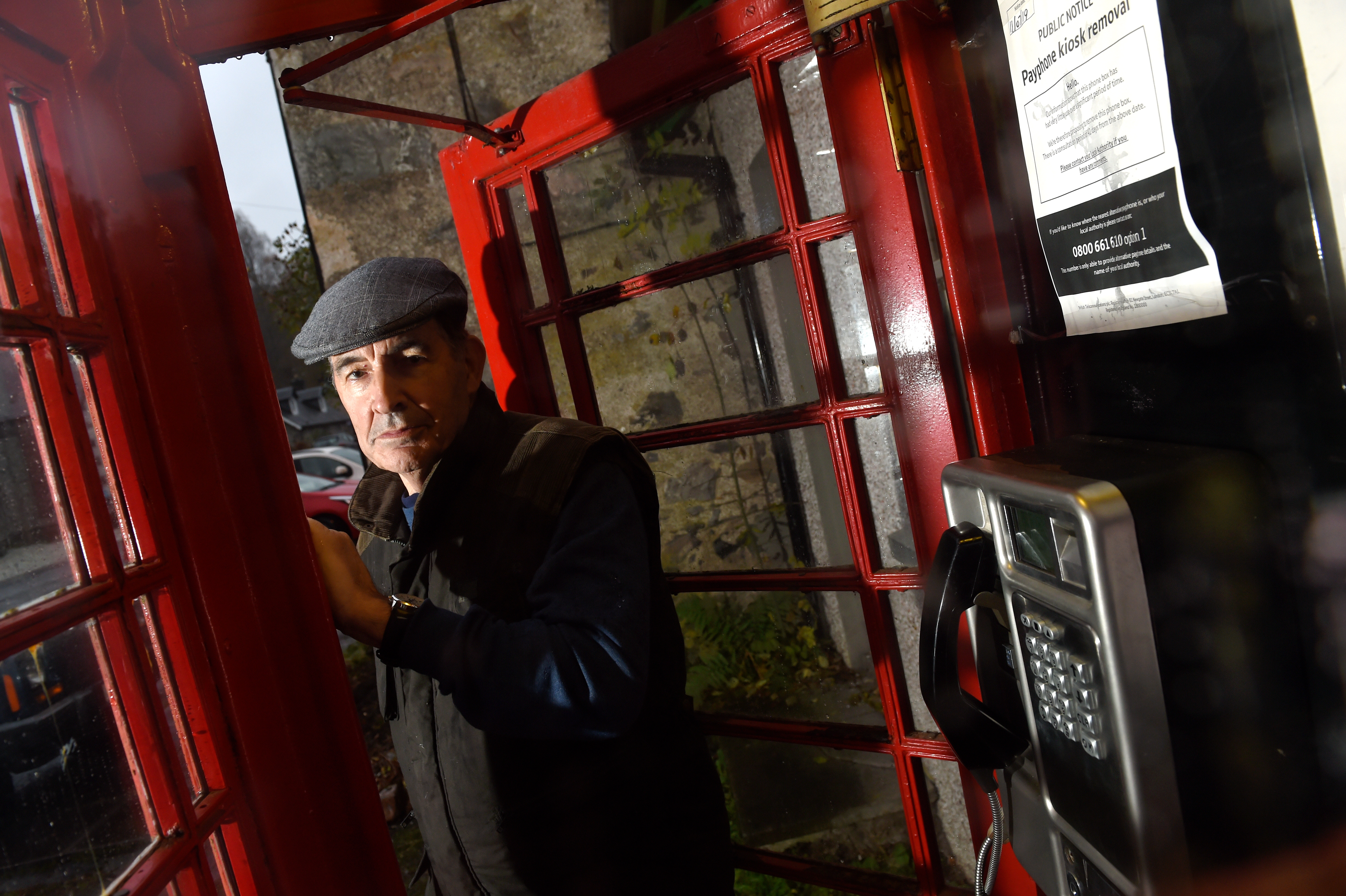 Peter Small, owner of the Tomich Hotel in the adjacent red telephone box, targeted for closure in 2019. Picture by Sandy McCook.