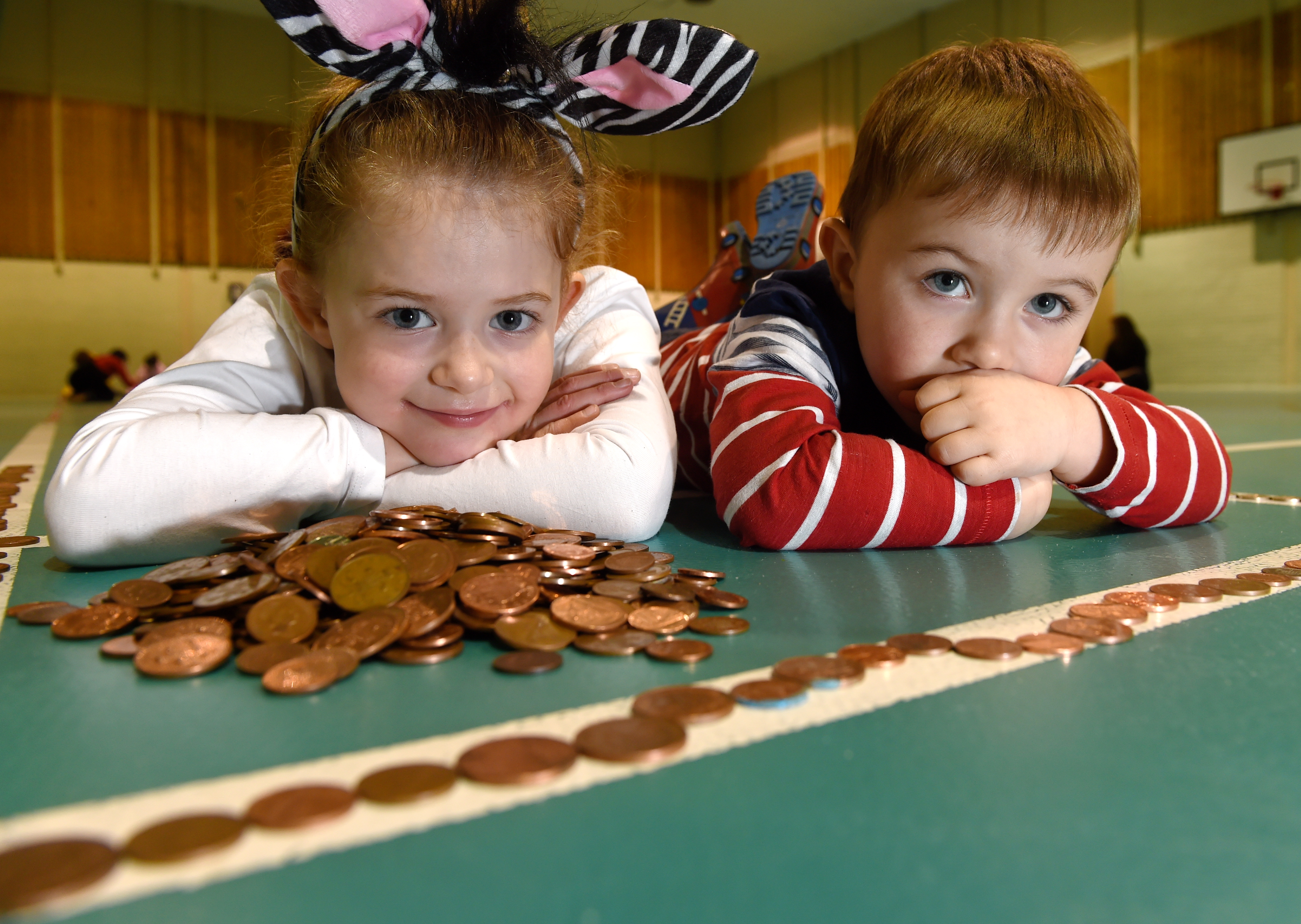 Thea McCulloch and Ethan Murray of Lossiemouth lend a hand to lay out the hundreds of yards of coins on the floor of Lossiemouth Community Centre. Picture by Sandy McCook