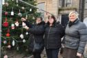 ISOBEL ARTHUR-ROBERTSON PUTS UP A HAND KNITTED DECORATION ON THE PETERHEAD CHRISTMAS TREE WATCHED BY FELLOW MEMBERS OF THE PETERHEAD SOCIAL KNITWORK ALISON MACLEAN,   AND FIONA BUCHAN