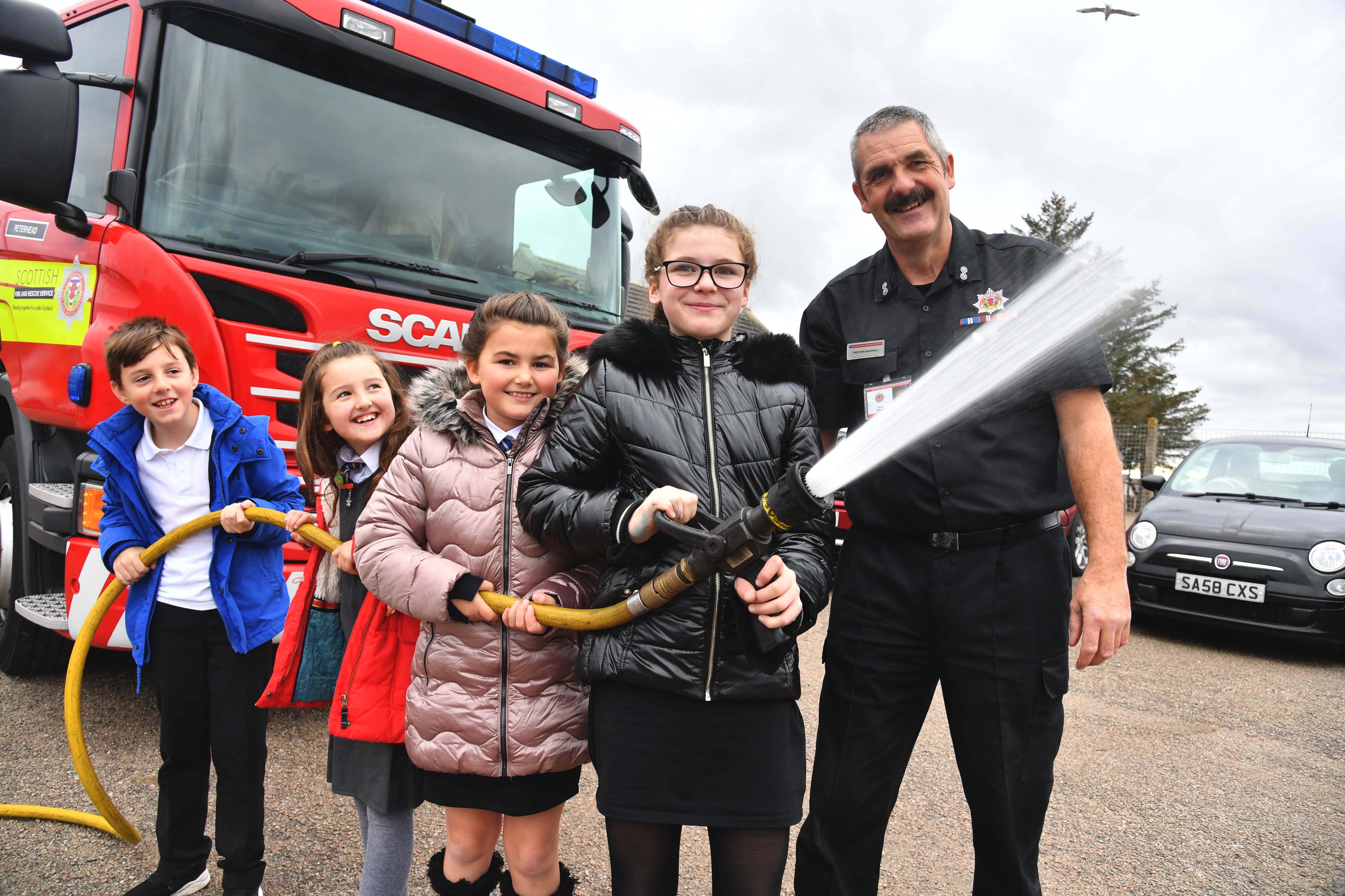 St Fergus Primary pupils (L-R) Clayton Smith, Georgie Robertson, Mylee Hastie and Bethany Duthie get hands on with a fire hose under the watchful eye of Peterhead firefighter Trevor Ashwell