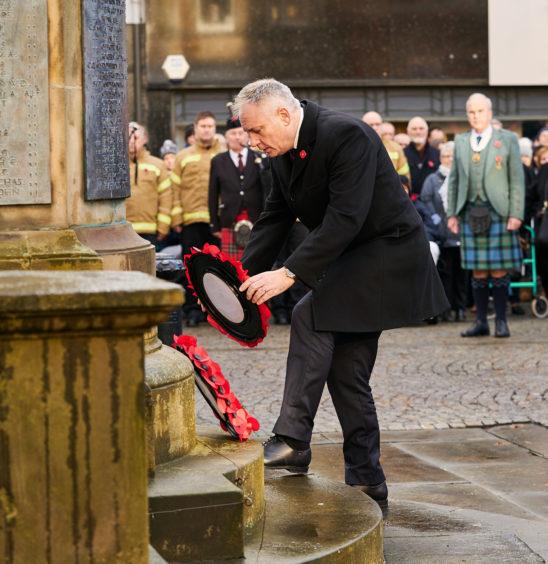 MSP Richard Lochhead lays a wreath in Elgin