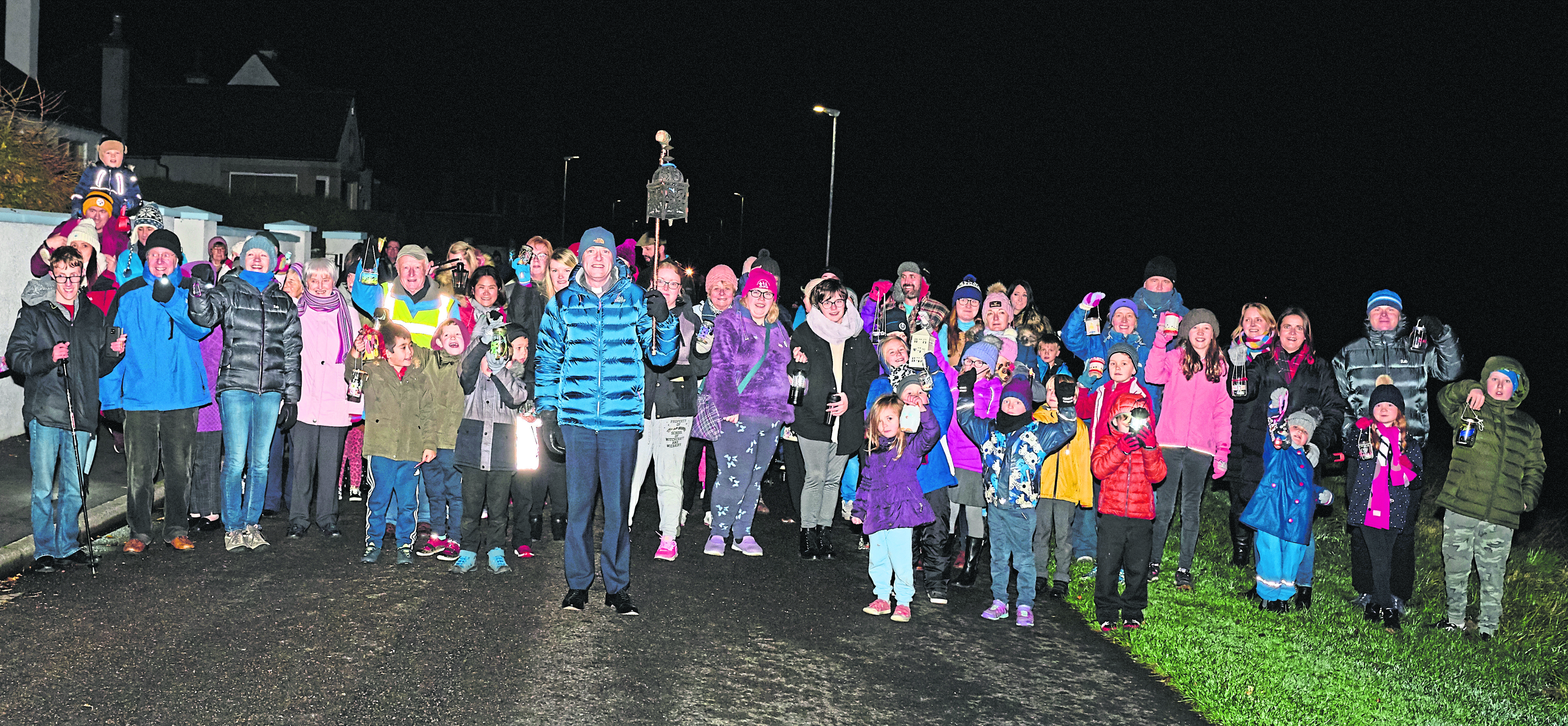 The St Gerardines Lantern Walk as it arrives at St Gerardines Church in Lossiemouth led by Rev Geoff McKee holding aloft his lantern.