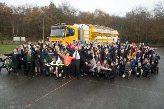 Pupils of Cults Primary with the big 18-wheel gritter which has been named with their entry – The Gritest Showman. Pictured at the front are Lord Provost of Aberdeen Barney Crockett and P6 pupil, 10-year-old Oliver Ironside, who came up with The Gritest Showman suggestion for the school