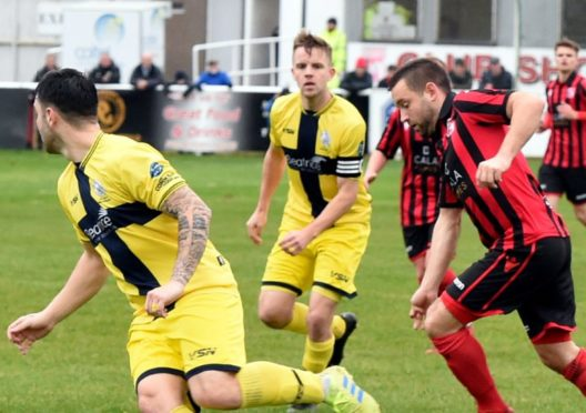 Neil Gauld runs through the Wick defence.  Picture by Jim Irvine