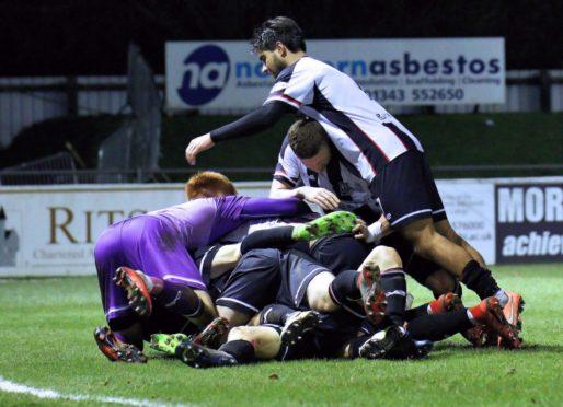 Elgin's final goalscorer Daniel McKay is buried below most of his team-mates celebrating his goal.
