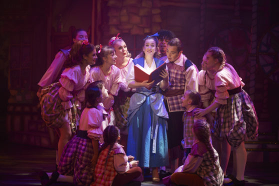 Belle, played by Christie Gowans, reads a story to the villagers.