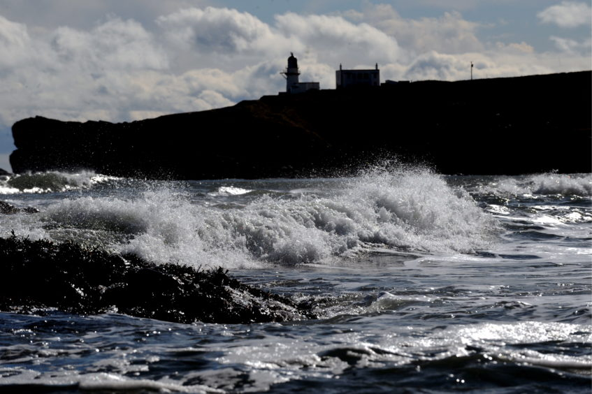 Todhead Lighthouse seen over Catterline Bay Picture by Chris Sumner.