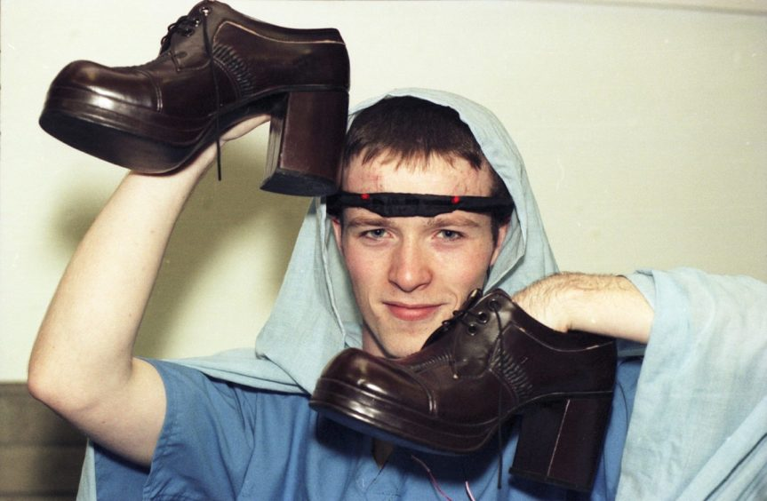 Mark Smith holding shoes for Elgin High School Pantomime in 1998.