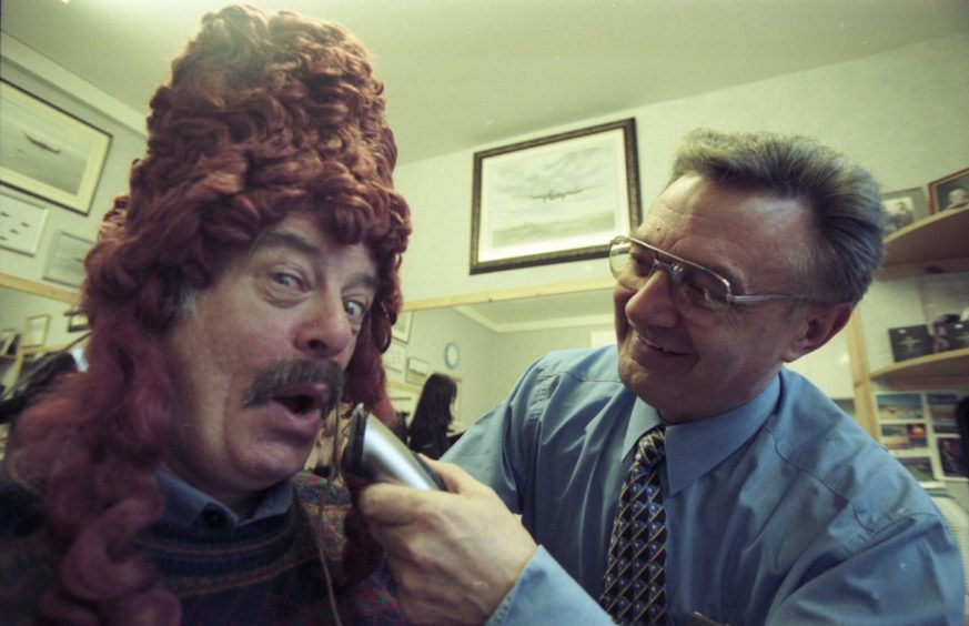 Jimmy Cameron, playing the ugly sister in the Cinderella Pantomime has his moustache shaved off by Tom Smith, the baron in 1999.