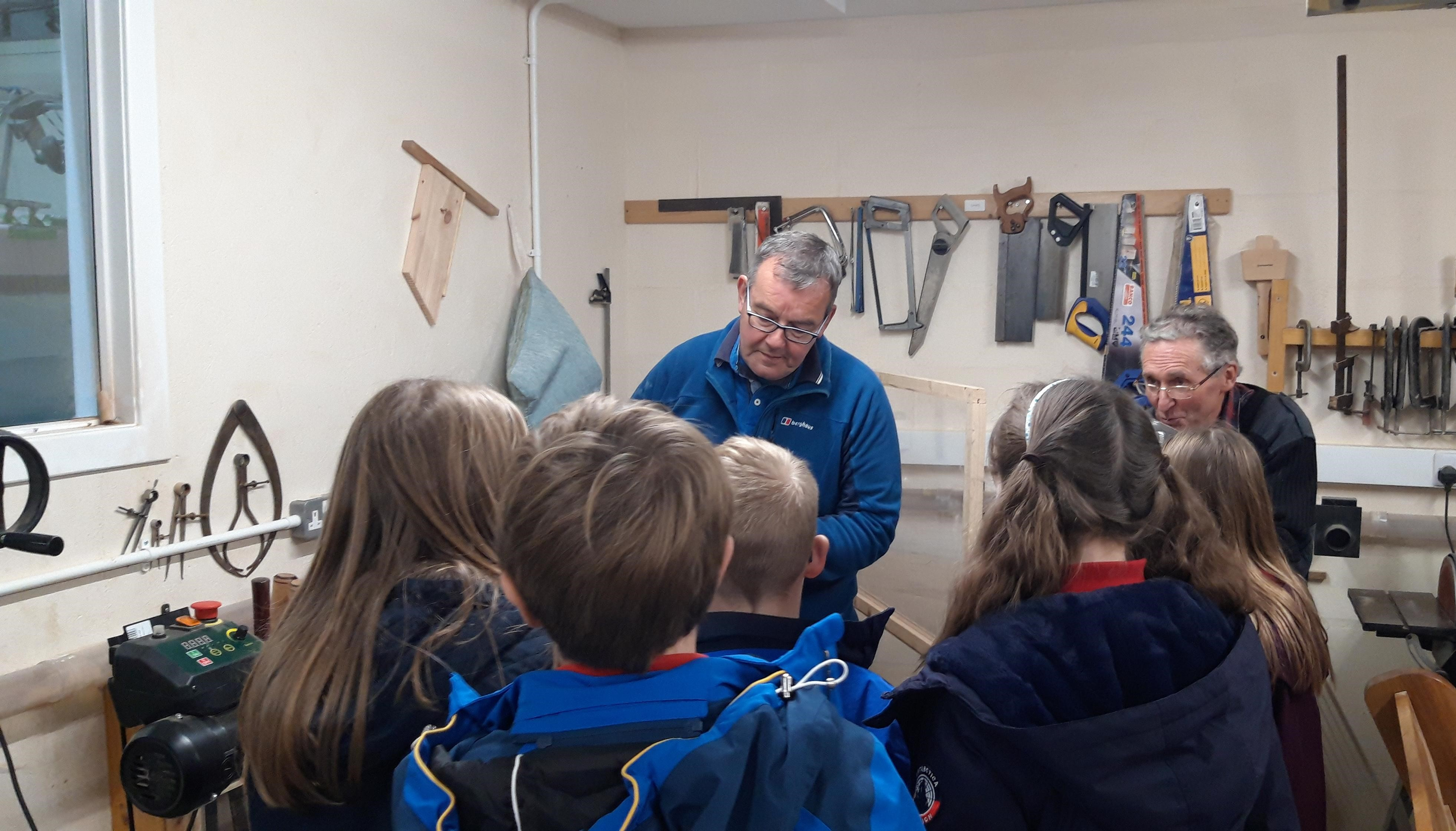 Chairman Steve Bramwell (Left) and member Michael Hutcheson giving primary six pupils from Avoch Primary School the grand tour of the Black Isle Men's Shed last year.