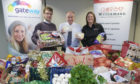 Craig Riddle, Gateway finance manager, David Sutherland, Food For Families founder, and Louise Beattie, sales manager for Williamson Foodservice with the food items ready for distribution