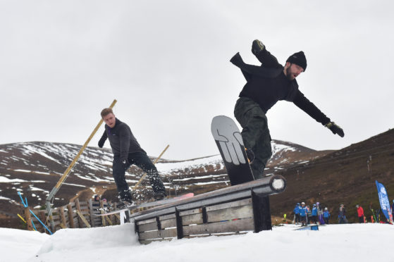 Local snow boarders and brothers Jamie  and Angus Trinder from Aviemore use the rail to get air. Picture by Jason Hedges