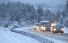 Traffic on the A9 near Inverness as heavy snow falls across the Highlands.