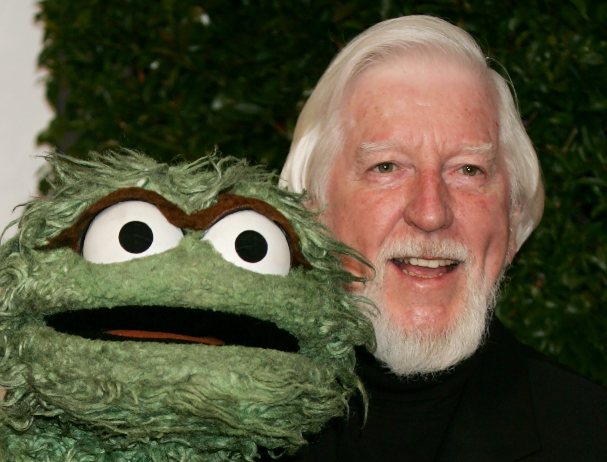 """FILE - In this Thursday, April 27, 2006, file photo, Caroll Spinney, right, who portrays """"Sesame Street"""" characters Oscar The Grouch, left, and Big Bird, arrives for the Daytime Emmy nominee party at the Hollywood Roosevelt Hotel in Los Angeles. Spinney, who gave Big Bird his warmth and Oscar the Grouch his growl for nearly 50 years on """"Sesame Street,"""" died Sunday, Dec. 8, 2019, at the age of 85 at his home in Connecticut, according to the Sesame Workshop. (AP Photo/Reed Saxon, File)"""