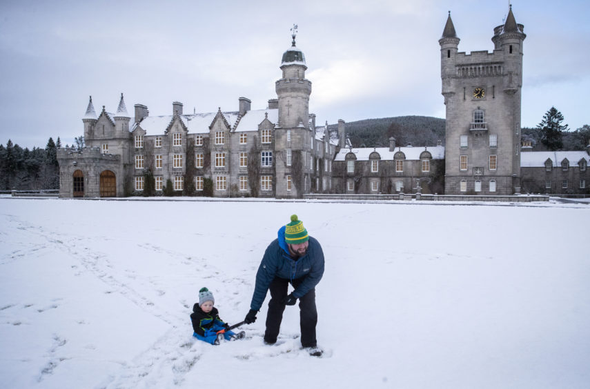 Geraint Stone pulls his two-year-old son Arthur on his sledge across the snow-covered lawn in front of Balmoral Castle, Royal Deeside.