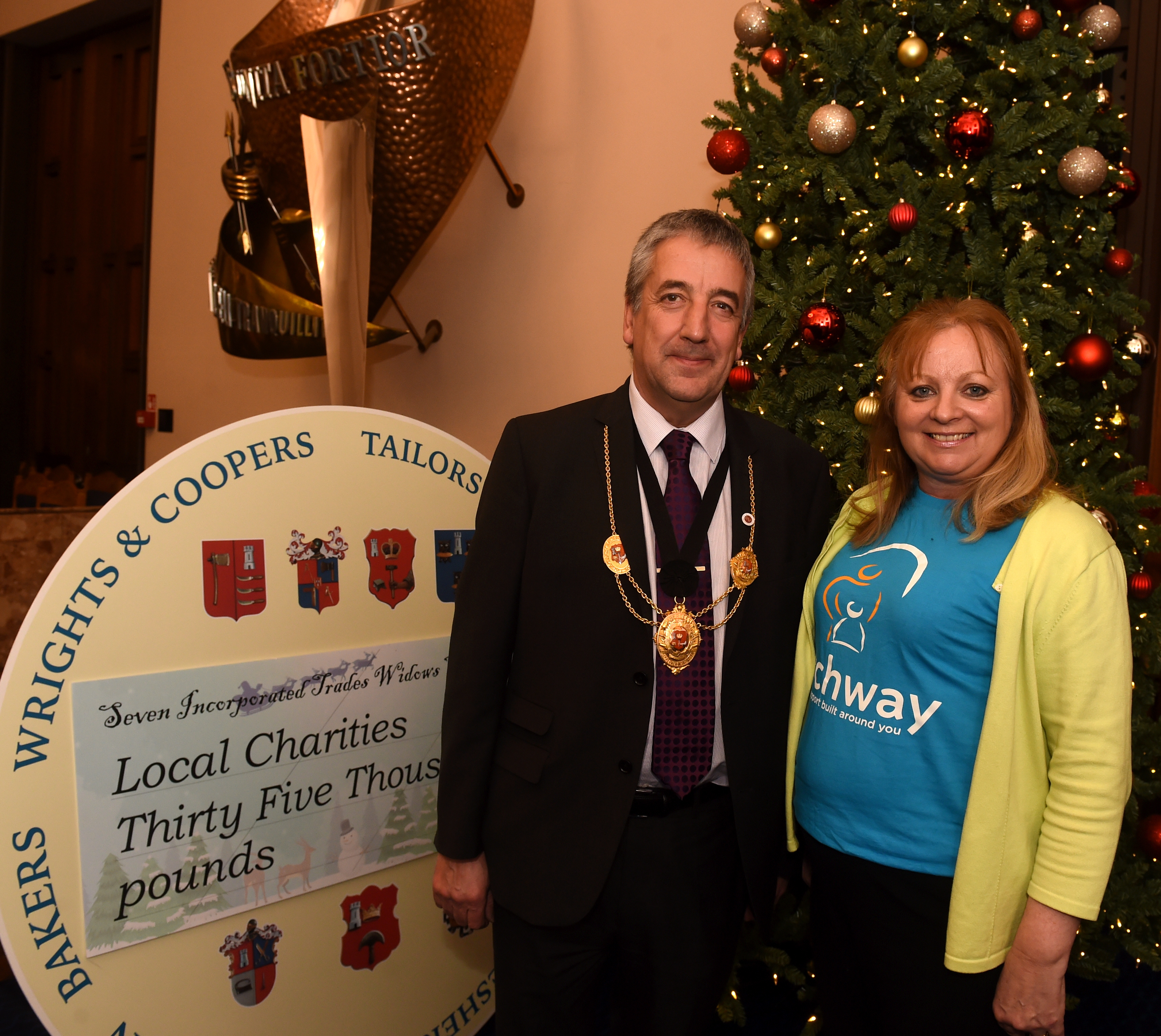 Archway's PR and fundraising manager Janin Davies recieves £1,667 from Alan Law, deacon of the Hammermen.