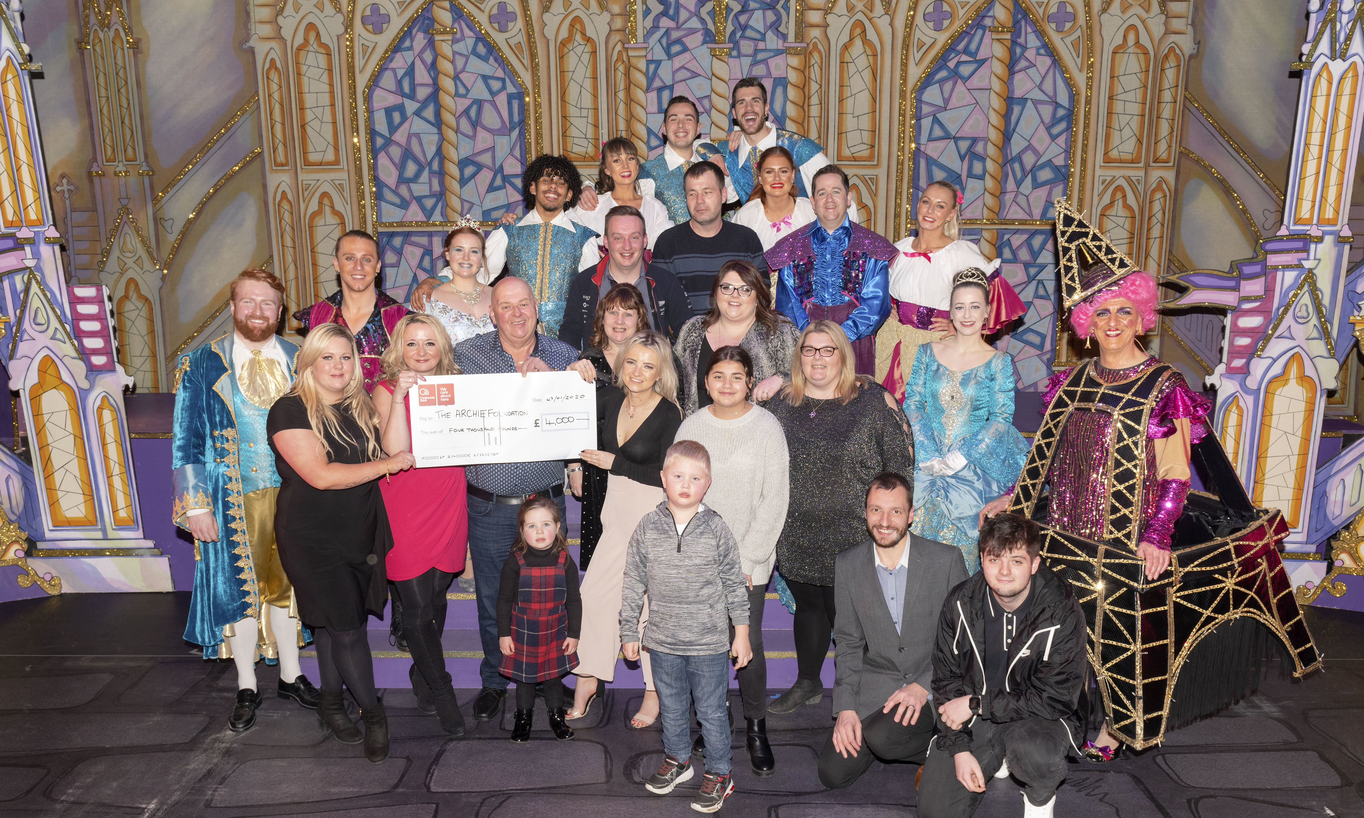 Donald Mathieson with the £4000 cheque presented to Mary Nimmo and Archie Highland fundraiser Dawn Cowie, alongside friends, family and cast members.
