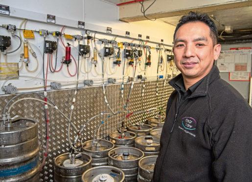 Wai Tsang at work in the beer cellar.