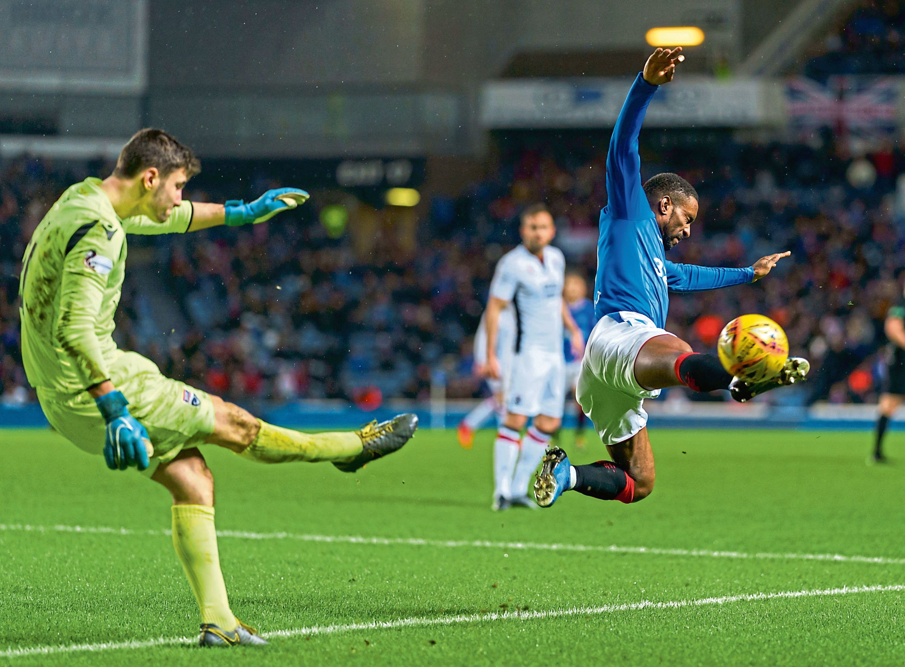 Jermain Defoe of Rangers tries to block a clearance from Ross County goalkeeper Nathan Baxter.