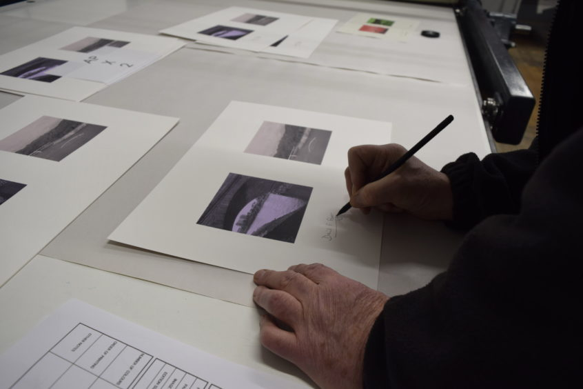 David Fryer signing the resulting print with Printmaker James Vass, at Peacock Visual Arts.